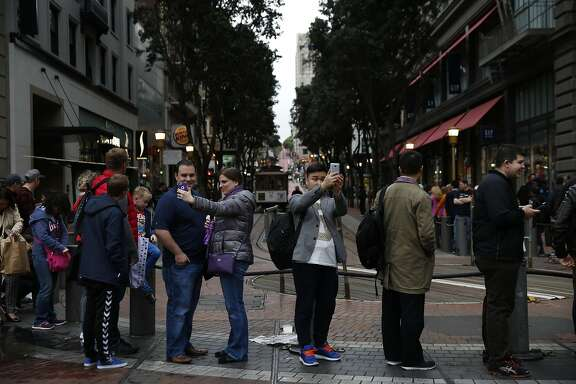 People take selfies while waiting for a cable car on Powell street March 3, 2016 in San Francisco, Calif.