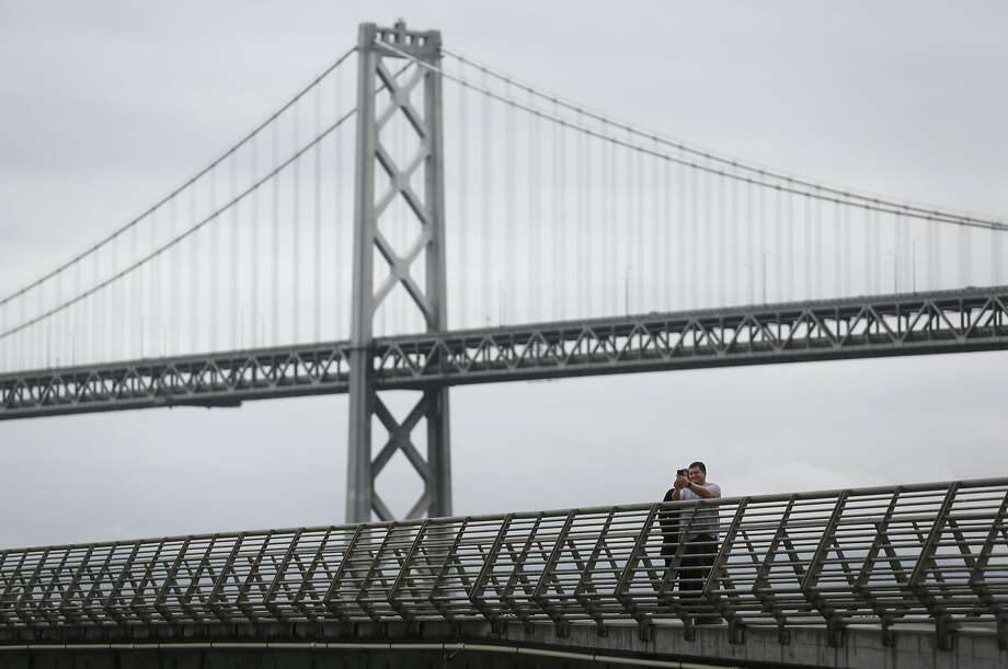 A man and a woman take a selfie with the Bay Bridge behind them March 3, 2016 in San Francisco, Calif. Photo: Leah Millis Leah Millis, The Chronicle