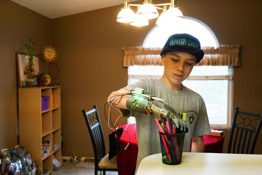 Kieran Coffee demonstrates how much weight his 3-D-printed prosthetic hand can lift in his family's Watsonville home. Photo: James Tensuan, Special To The Chronicle