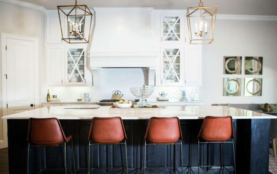 The marble-topped island and leather barstools make the kitchen an extension of the living room. Photo: Marie D. De Jesus, Staff / © 2016 Houston Chronicle