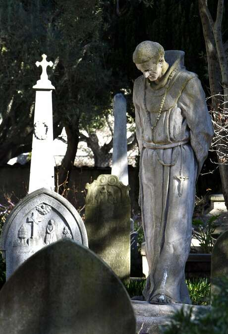 A statue of the Rev. Junipero Serra stands in a cemetery, which still exists at Mission Dolores. Photo: Lance Iversen, The Chronicle
