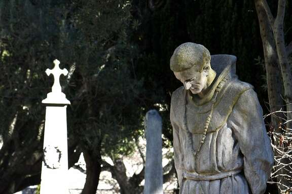 A Statue of Father Junipero Serra stands in the middle of the church cemetery at Mission Dolores in San Francisco on Tuesday, Jan 13, 2009.