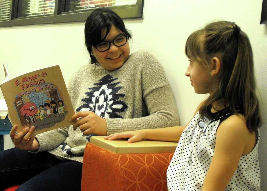 "Fabiana Bracho, left, reads her book, ""El Mundo de Escritura World of Writing,"" to seven-year-old Aliza Sobotic, a first-grader at Fielder Elementary School."
