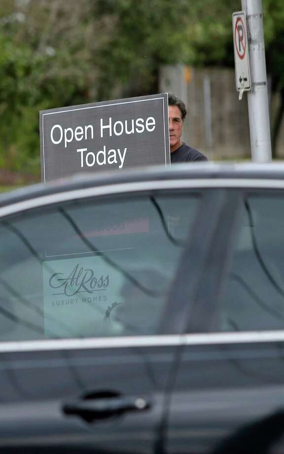 Ken McDermogg holds a sign at the corner of San Felipe and Kirby advertisting an open house in February. ( Melissa Phillip / Houston Chronicle ) Photo: Melissa Phillip, Staff / © 2016 Houston Chronicle