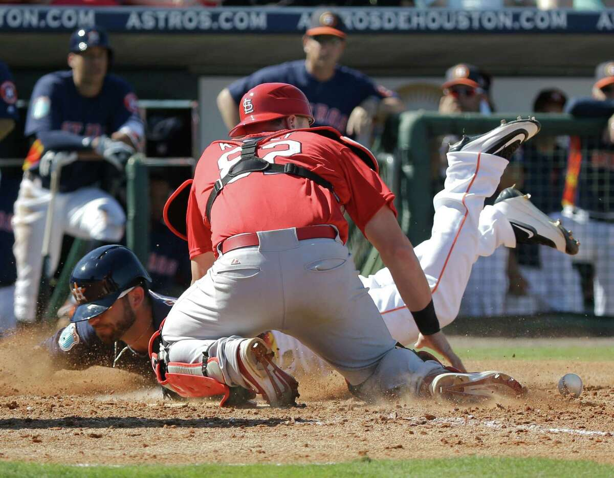 Houston Astros' Andrew Aplin, back, slides home as St. Louis Cardinals catcher Carson Kelly (82) drops the ball in the fifth inning of a spring training baseball game, Friday, March 4, 2016, in Kissimmee, Fla.