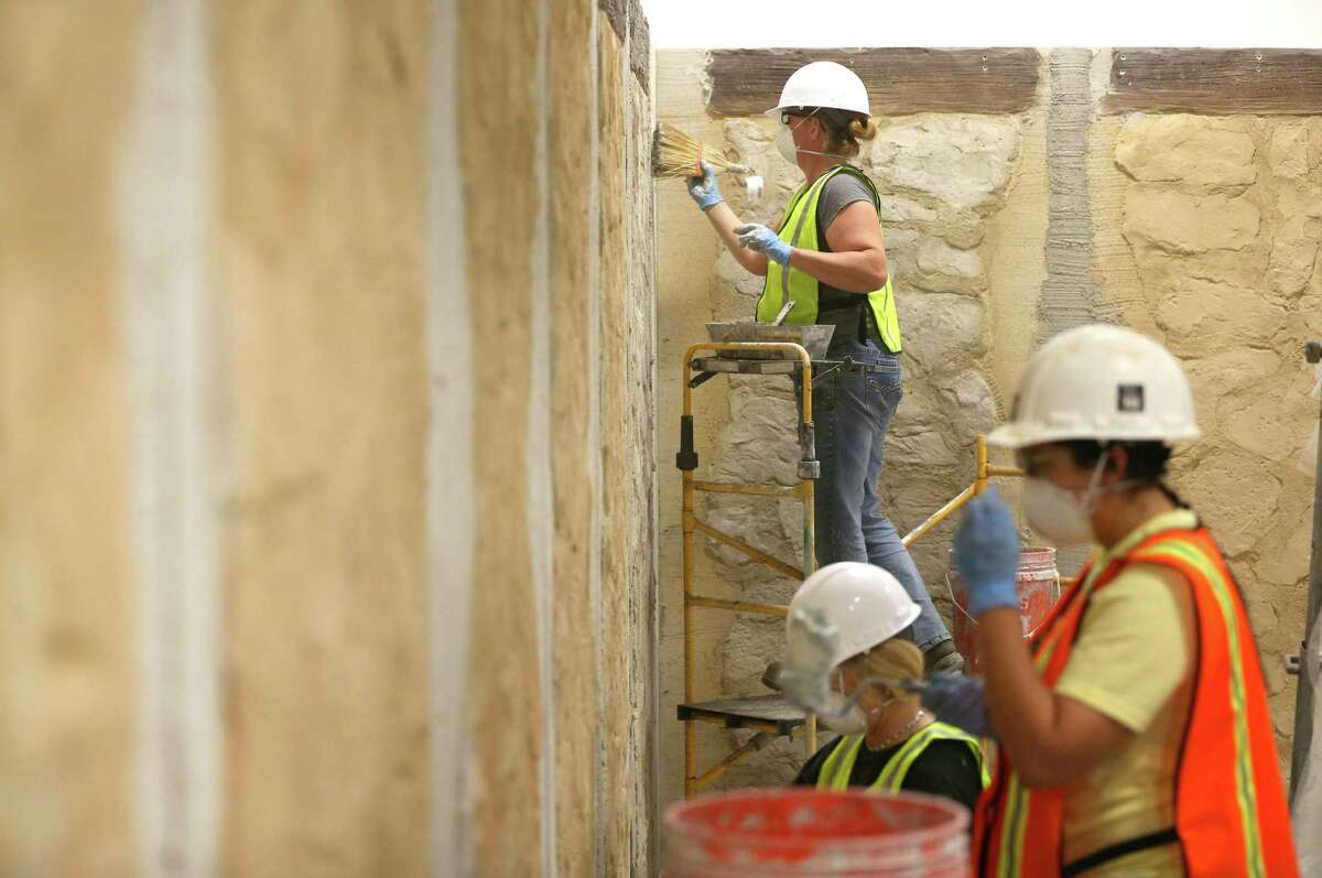 Employees from SRO Associates, Inc. install fake rock walls Wednesday, Feb. 17, 2016 in the