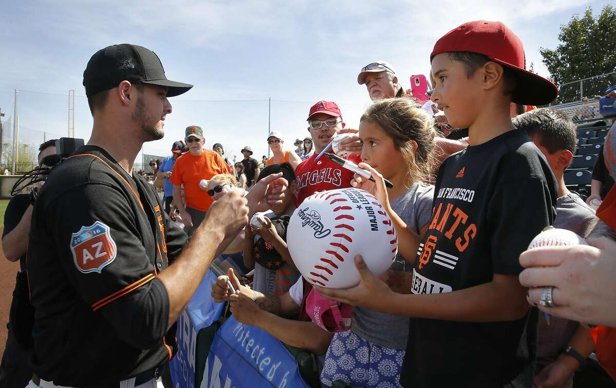 Pitcher Tyler Beede, 63 signs a giant base for Jamison and Kylie Husbands of San Clemente, Ca. as the San Francisco Giants prepare to play the Los Angeles Angels at Scottsdale Stadium on Wed. March 2, 2016, in Scottsdale, Arizona.