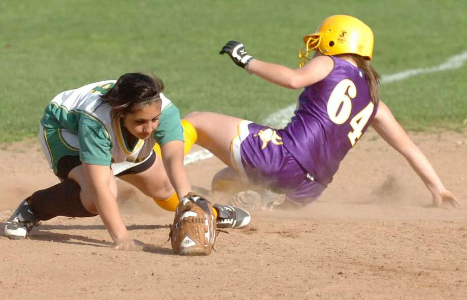 Westhill's Cassandra Kish slides safely into third as Trinity's Krissy Schule covers the base as Trinity Catholic hosts Westhill High School in a girls softball game Thursday afternoon, April 8, 2010. Westhill won the game 4-0. Photo: Keelin Daly / Stamford Advocate