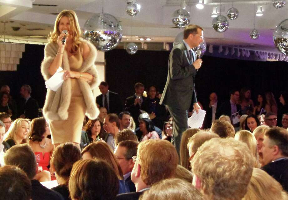 "Near & Far Aid gala emcee Dave Price, an NBC weatherman, and co-host Elyse Luray, auctioneer and personality on the PBS show ""History Detectives,"" lead auction bidding at Mitchell's of Westport during the charity's annual spring fundraiser. Photo: Contributed Photo / Meg Barone / Westport News"