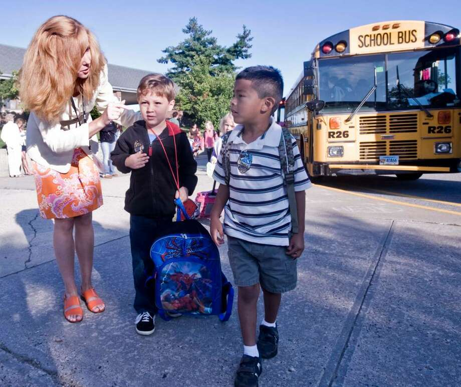 Redding Elementary School principal Stephanie Pierson Ugo assists kindergartner Keith Cabot and first grader David-Lovenzo Plunske in finding their way after departing the bus on the first day of school. Wednesday, Sept. 2, 2009 Photo: Scott Mullin / The News-Times