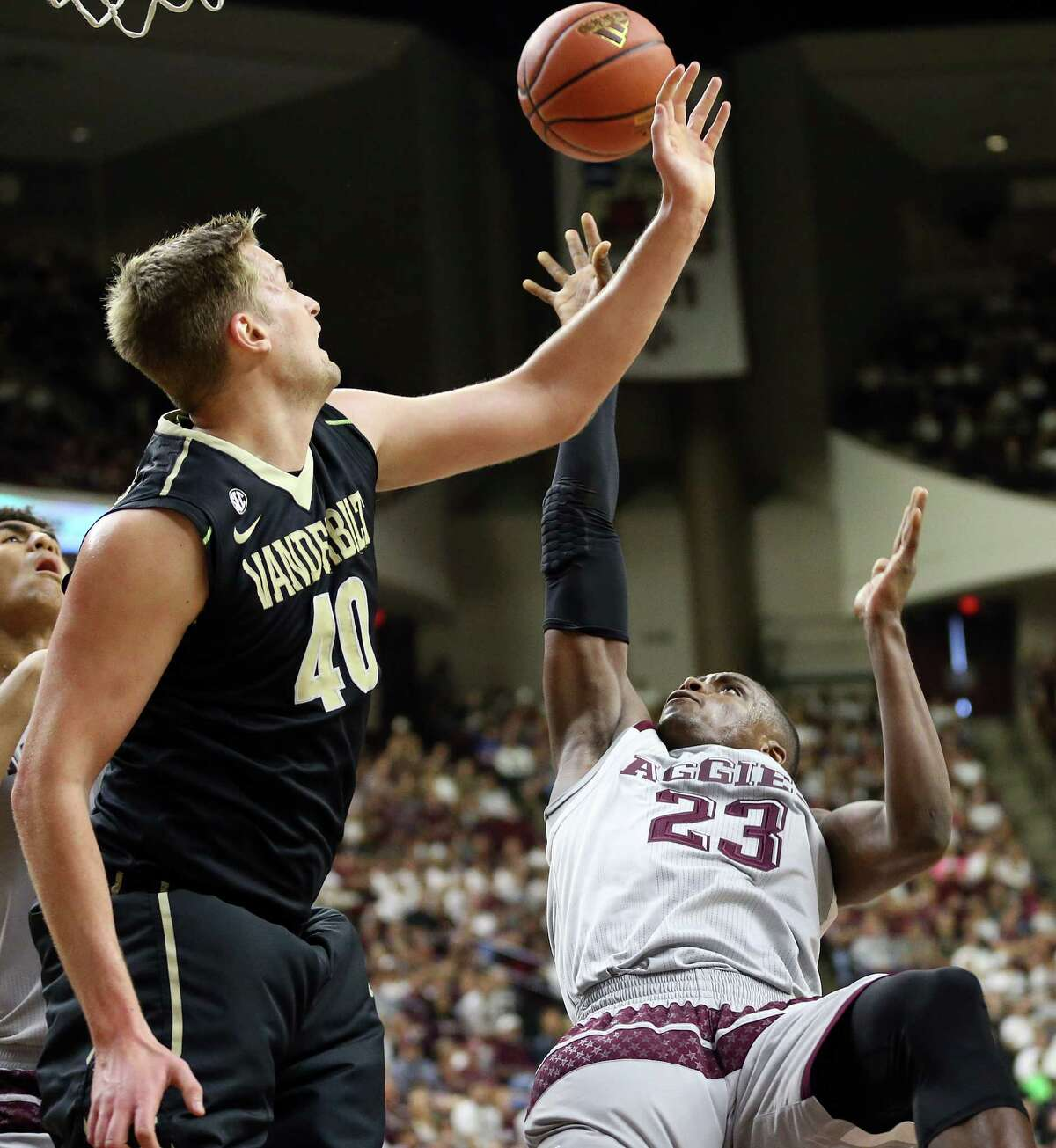 Texas A&M's Danuel House (23) is fouled by Vanderbilt's Josh Henderson (40) while making a shot during the first half of an NCAA college basketball game, Saturday, March 5, 2016, in College Station, Texas.