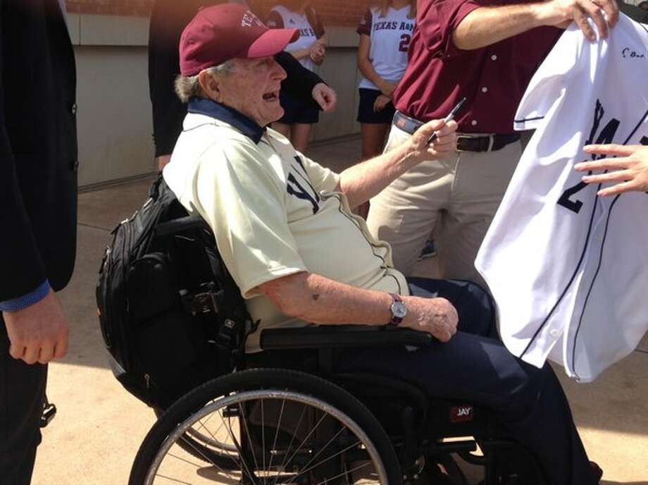 Former President George H.W. Bush signs an autograph after throwing out the first pitch at Saturday's Yale vs. Texas A&M baseball game in College Station. (Brent Zwerneman / Houston Chronicle)