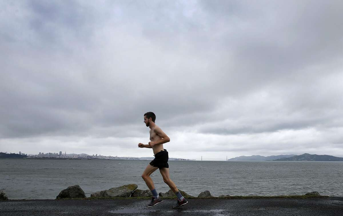 A hearty jogger runs along the shoreline at Cesar Chavez Park in Berkeley, Calif. on Saturday, March 5, 2016 shortly before the first of a series of major rainstorms drenches the Bay Area.