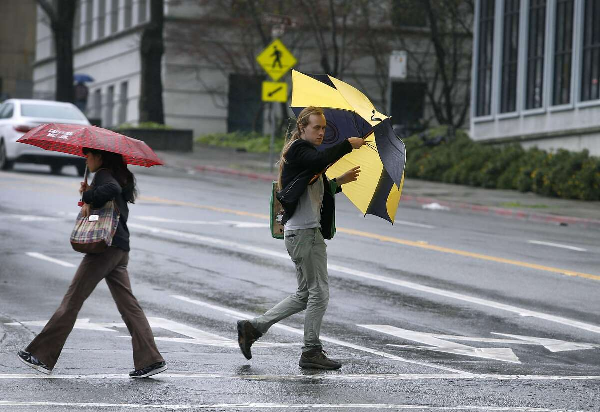 A man crossing Hearst Avenue keeps his umbrella from inverting in the wind in Berkeley, Calif. on Saturday, March 5, 2016 in the first of a series of major rainstorms that are expected to drench the Bay Area.