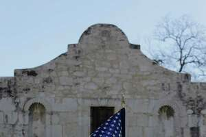 """The U.S. flag waves in front of the Alamo during a reenactment of the delivery of William B. Travis' """"Victory or Death"""" letter, Wednesday, Feb. 24, 2016, in San Antonio.  The Alamo is commemorating the 180th anniversary of the siege and battle of the Alamo. (AP Photo/Eric Gay)"""