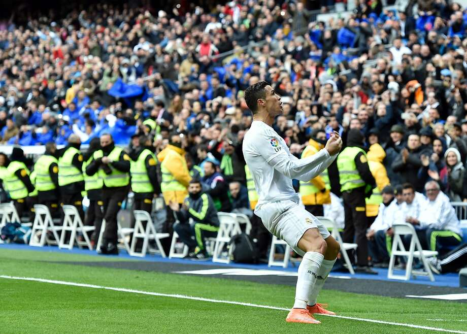 Madrid fans are passionate about soccer, as when Real's Cristiano, above, scored his third goal Saturday at Bernabeu. Photo: GERARD JULIEN, AFP/Getty Images