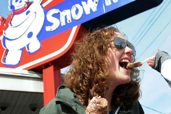 "Allison Bishop of Troy, with cone in hand, gets a taste of an ice cream treat from her cousin Catherine Foley on Saturday, March 5, 2016, at Snowman Ice Cream in Troy, N.Y. The cousins were there for the seasonal opening day, which Bishop said was ""like Christmas – best day of the year.""  (Cindy Schultz / Times Union)"