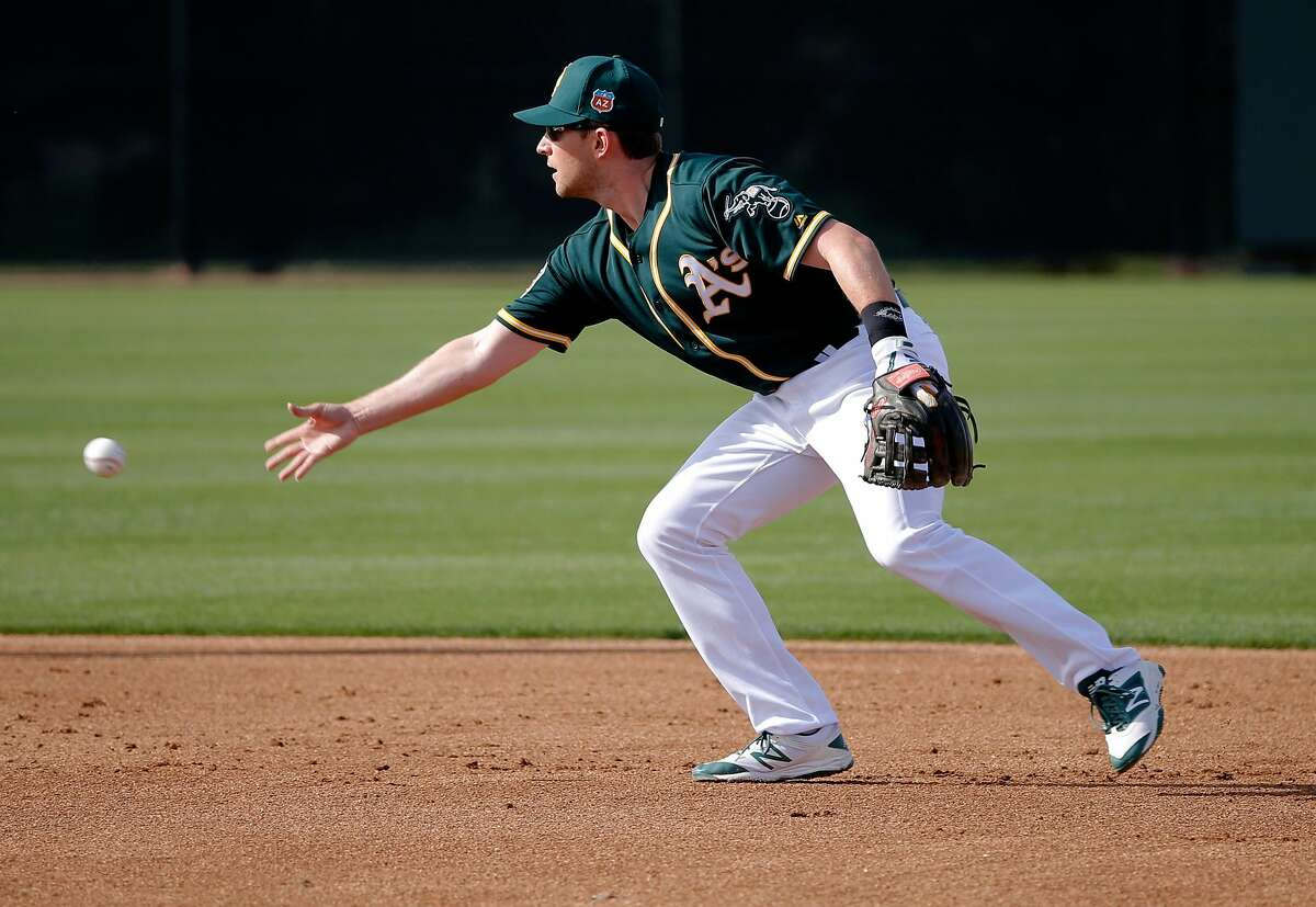 Infielder Jed Lowrie tosses to second base during drills at the A's 2016 spring training.