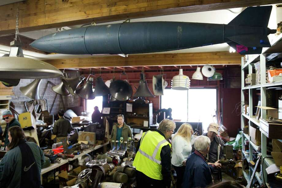 A large, dummy bomb hangs from the ceiling of an estate sale filled with World War II era goods, in Greenlake on Saturday, March 5, 2016. Photo: GRANT HINDSLEY, SEATTLEPI.COM / SEATTLEPI.COM