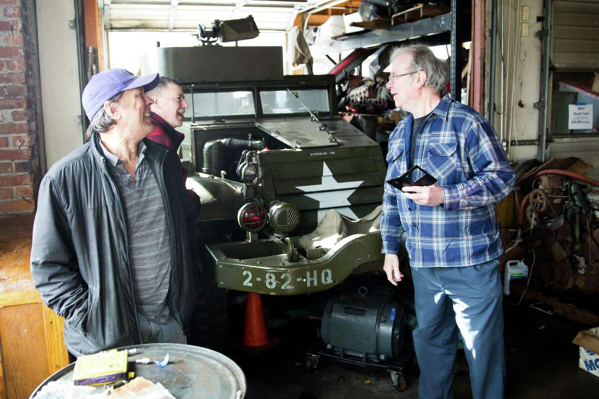 Shoppers laugh while talking around a 1945 White Half-Track military vehicle that reportedly sold to Paul Allen, at an estate sale filled with World War II era goods, in Greenlake on Saturday, March 5, 2016.