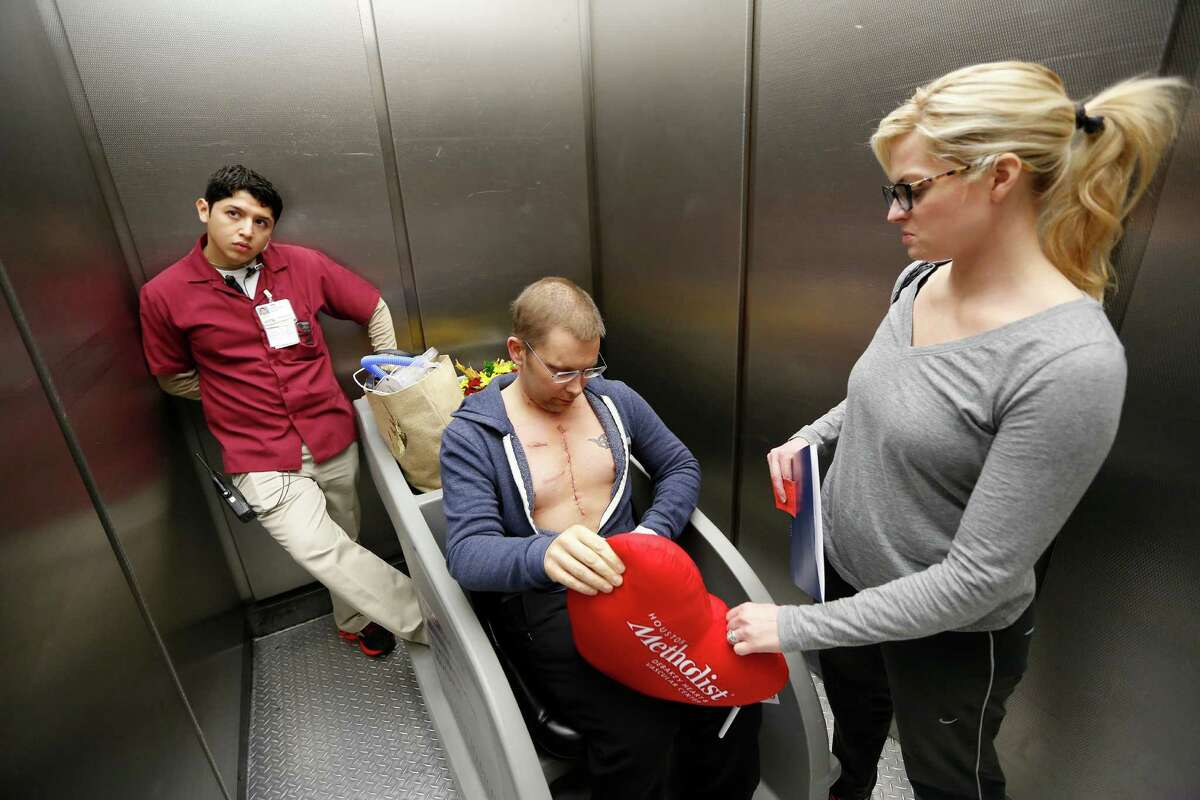Chriss Schwiderski , 36, went to the emergency room in 2014 with severe chest pain. Several months later, he was diagnosed with cardiac sarcoma. His tumor was removed with negative margins in November after months of chemotherapy. Methodist Hospital Patient Transportation Osvaldo Alquicira (left) helps Chriss Schwidierski and his wife, Jennifer leave the hospital, Saturday, Dec. 5, 2015, in Houston, 6 days after having a cancerous tumor removed from his heart.( Steve Gonzales / Houston Chronicle )