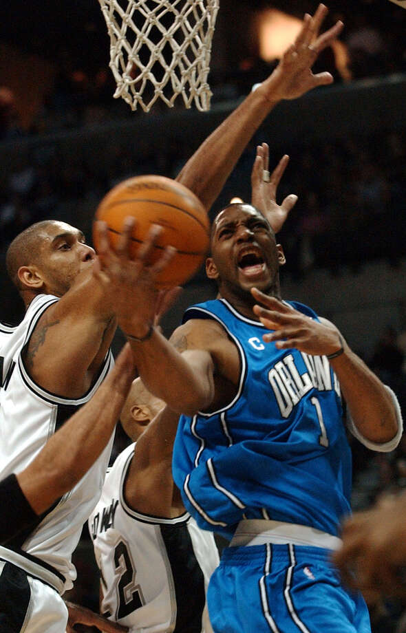 Orlando Magic guard Tracy McGrady is surrounded by Spurs forward Tim Duncan (left) and Bruce Bowen (center) during the first half on Dec 26, 2003, in San Antonio. Photo: Associated Press File Photo / AP