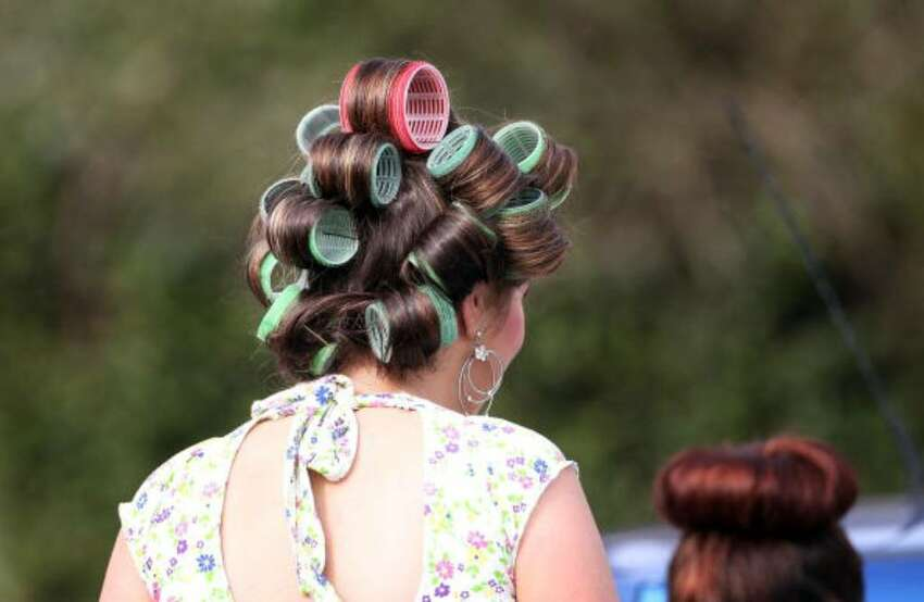 AINTREE, ENGLAND - APRIL 09: A lady dons giant curlers, the latest Merseyside fashion, outside Aintree race course in preparation for Ladies Day on April 9, 2010 in Aintree, England. Friday is traditionally Ladies day at the three-day meeting of the world famous Grand National, where fashion is as important as thne racing. (Photo by Christopher Furlong/Getty Images)