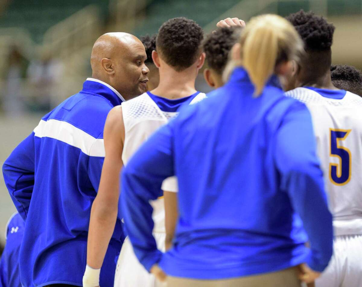 Elkins Knights Head Coach, Albert Thomas rallies his team in the first half against the Beaumont Ozen Panthers in high school basketball's 5A Region III finals on Saturday, March 5, 2016 at the Merrell Center.