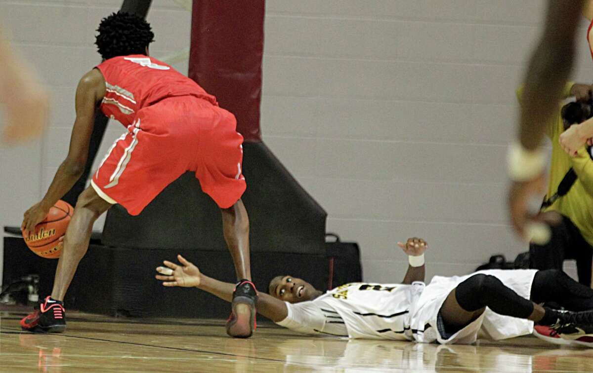 Sam Houston's Lennard Robinson right, dives for the ball after Cypress Lakes' De'Aaron Fox left, gained possession of a loose ball and during the Region 3 6A Regional Semi-Final Basketball Playoff game at Aldine ISD's Campbell Center Saturday, March 5, 2016, in Houston.