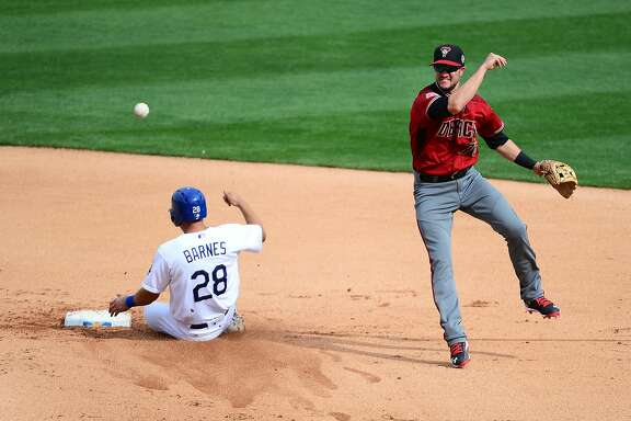 GLENDALE, AZ - MARCH 05: Jack Reinheimer #76 of the Arizona Diamondbacks turns the double play in the sixth inning over the sliding Austin Barnes #28 of the Los Angeles Dodgers during the spring training game at Camelback Ranch on March 5, 2016 in Glendale, Arizona. (Photo by Jennifer Stewart/Getty Images)