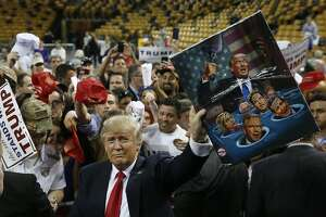 Republican presidential candidate Donald Trump shows off a gifts given to him by a supporter during a campaign rally, Saturday, March 5, 2016, in Orlando, Fla. (AP Photo/Brynn Anderson)
