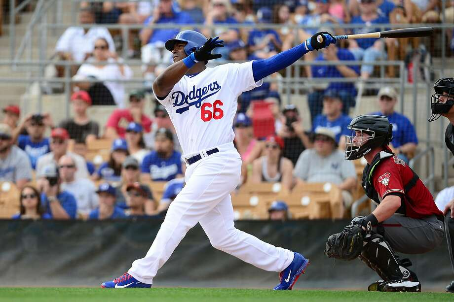 Yasiel Puig of the Los Angeles Dodgers hits a sacrifice fly ball driving in a run in the first inning against the Arizona Diamondbacks. Photo: Jennifer Stewart, Getty Images