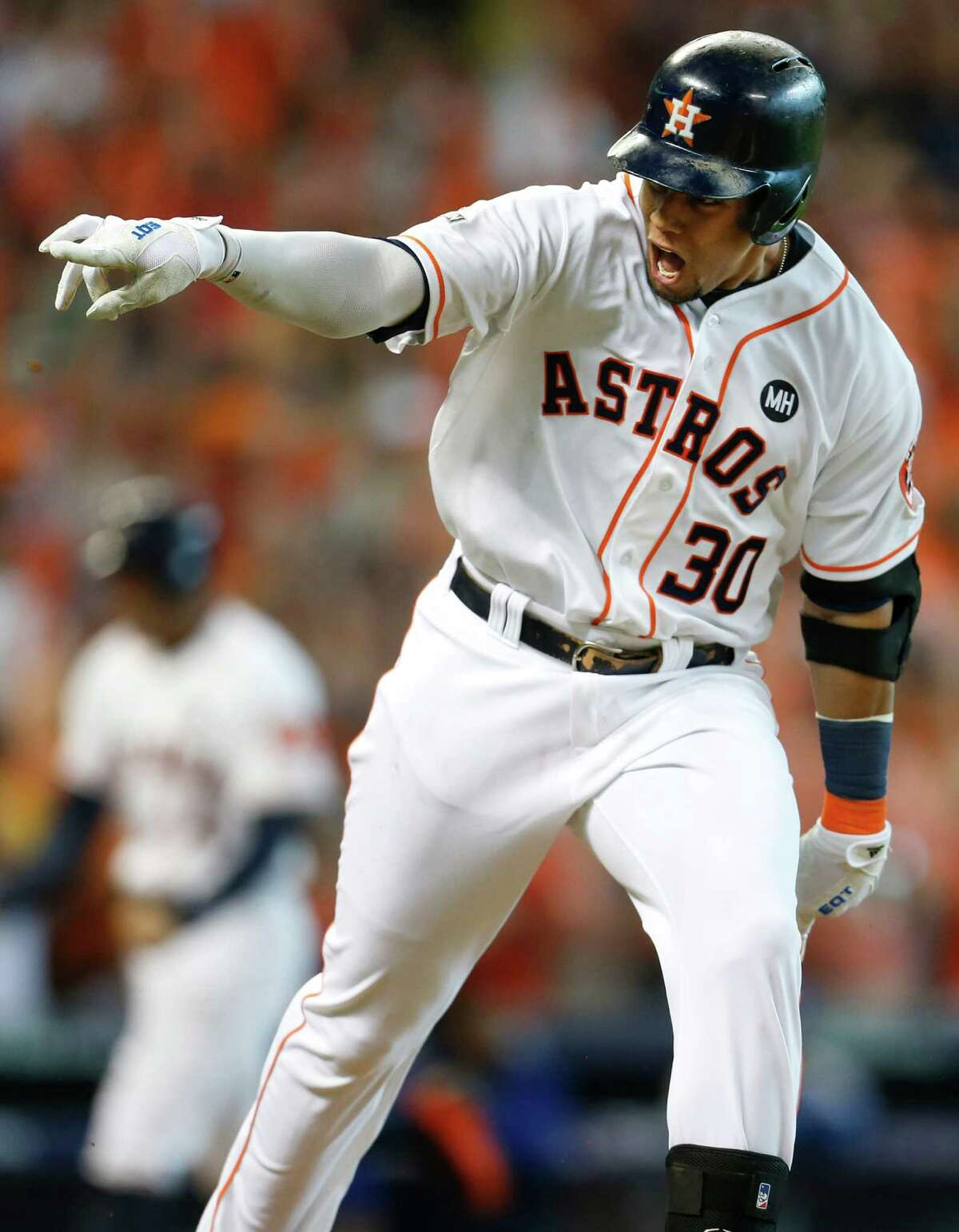 Houston Astros center fielder Carlos Gomez (30) points to the dugout after hitting an RBI single, scoring George Springer, off Kansas City Royals starting pitcher Edinson Volquez during the sixth inning of Game 3 of the American League Division Series at Minute Maid Park on Sunday, Oct. 11, 2015, in Houston. ( Karen Warren / Houston Chronicle )