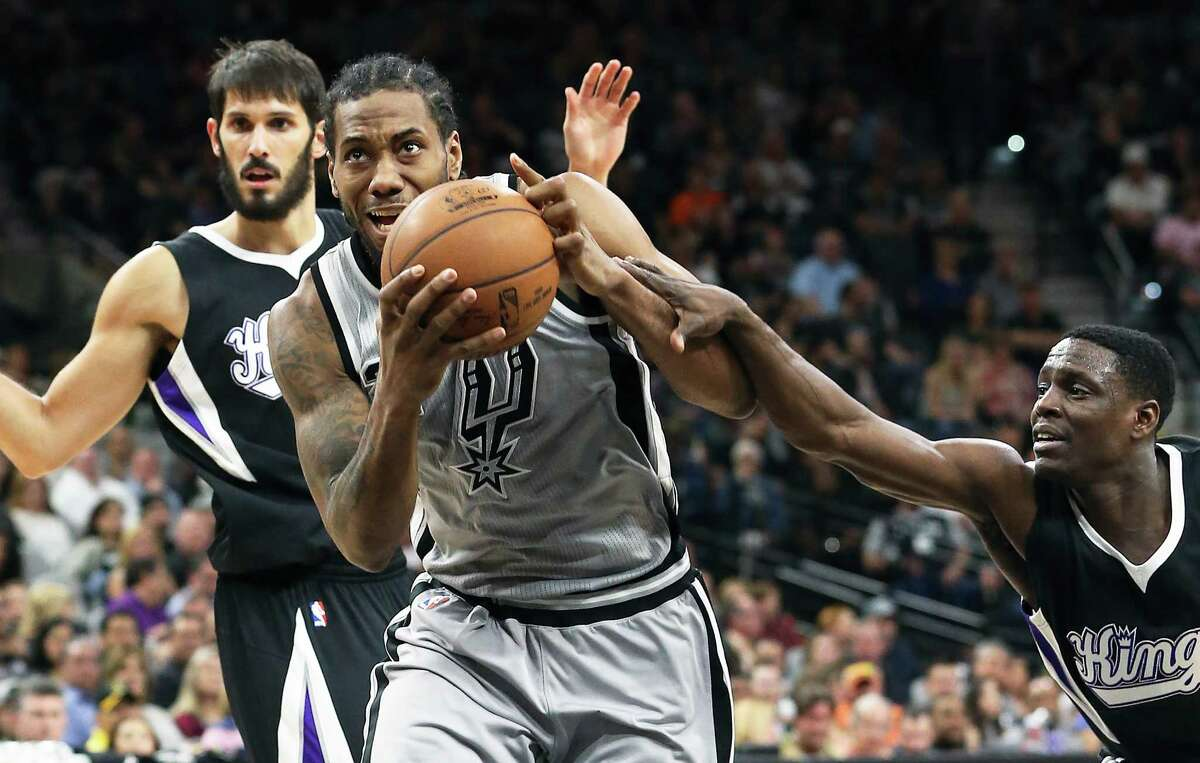 Kawhi Leonard gets fouled on a drive to the hoop by Darren Collison as the Spurs host Sacramento at the Alamodome on March 5, 2016.