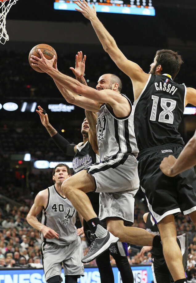 Manu Ginobili drives to the hoop under Omri Casspi as the Spurs host Sacramento at the Alamodome on March 5, 2016. Photo: TOM REEL, . / 2016 SAN ANTONIO EXPRESS-NEWS