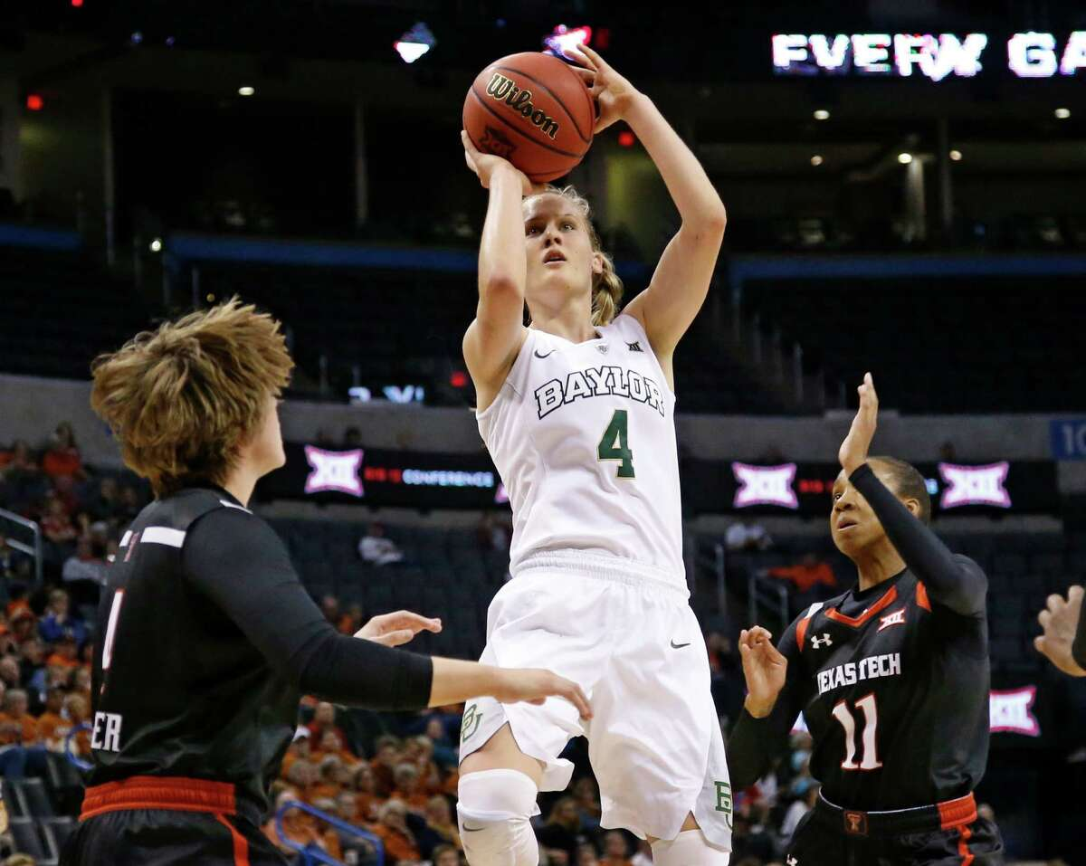 Baylor Bears guard Kristy Wallace (4) shoots between Texas Tech guard Ryann Bowser (4) and guard Rayven Brooks (11) in the second quarter.