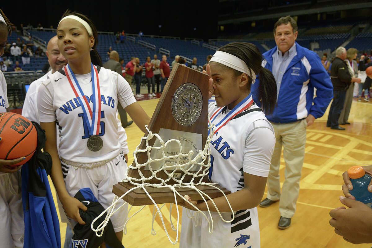Dekaney 5'2 senior guard Jaelyn Richard-Harris, right, with teammate Kalea Brooks, carries her team's state championship runner-up trophy after the Lady Wildcat's 76-42 loss to Duncanville in their Class 6A girls basketball state final at the Alamodome in San Antonio on Saturday, Mar. 5, 2016. (Photo by Jerry Baker/Freelance)