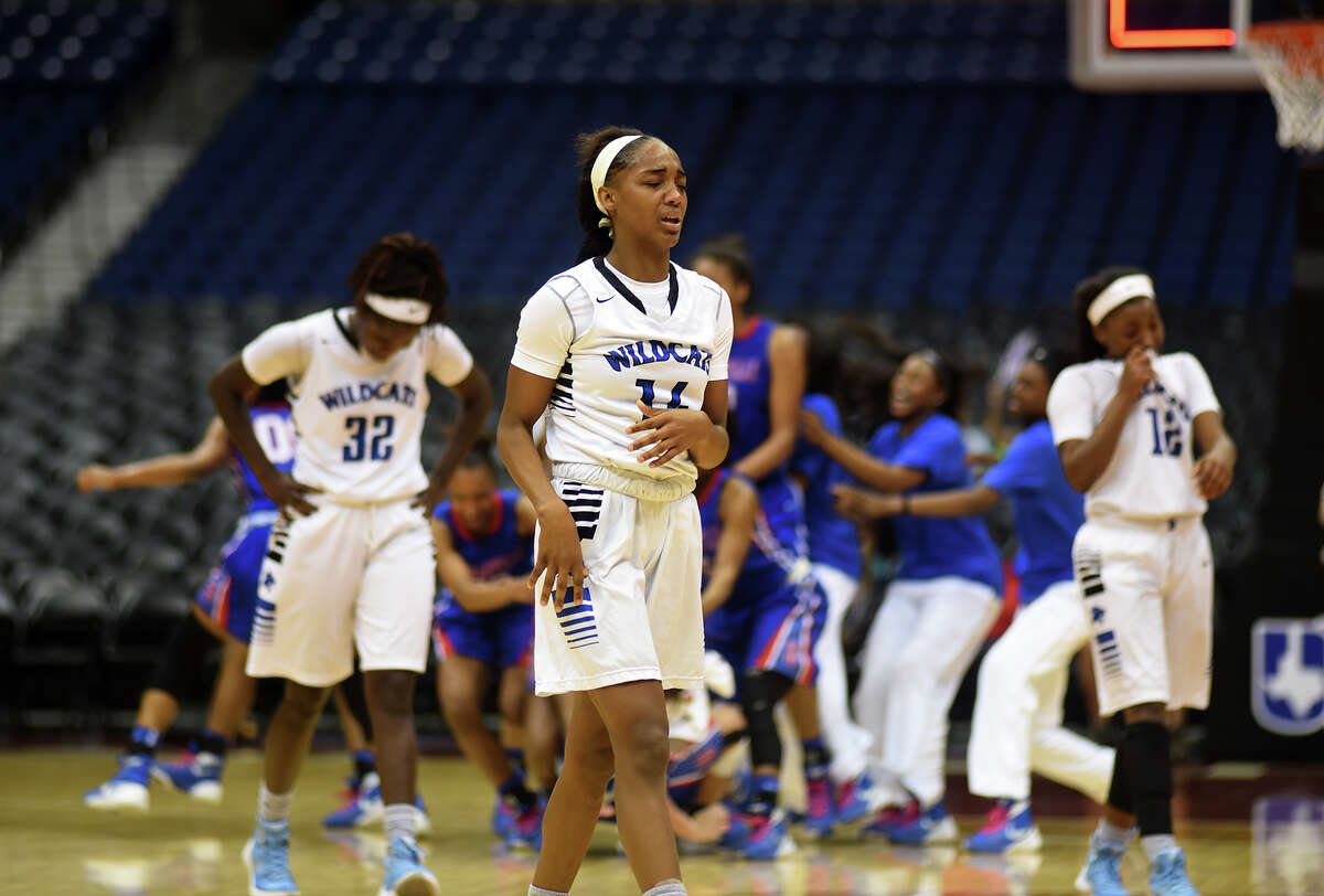 Dekaney junior guard Keishawna Scott, center, and her teammates walk off the court as the Duncanville Pantherettes celebrate their 76-42 win over the Lady Wildcats in their Class 6A girls basketball state final at the Alamodome in San Antonio on Saturday, Mar. 5, 2016. (Photo by Jerry Baker/Freelance)