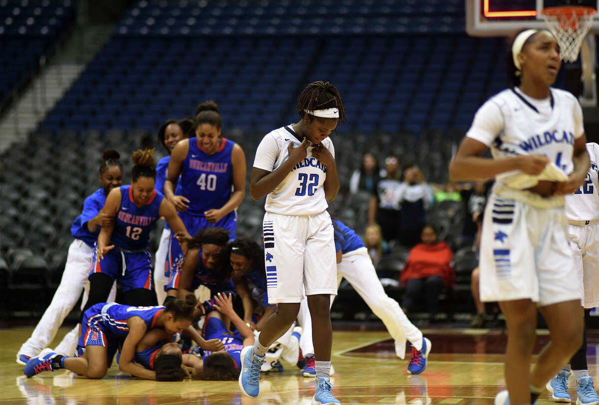 Dekaney senior forward Makeedah Collins (32) and her teammates walk off the court as the Duncanville Pantherettes celebrate their 76-42 win over the Lady Wildcats in their Class 6A girls basketball state final at the Alamodome in San Antonio on Saturday, Mar. 5, 2016. (Photo by Jerry Baker/Freelance)