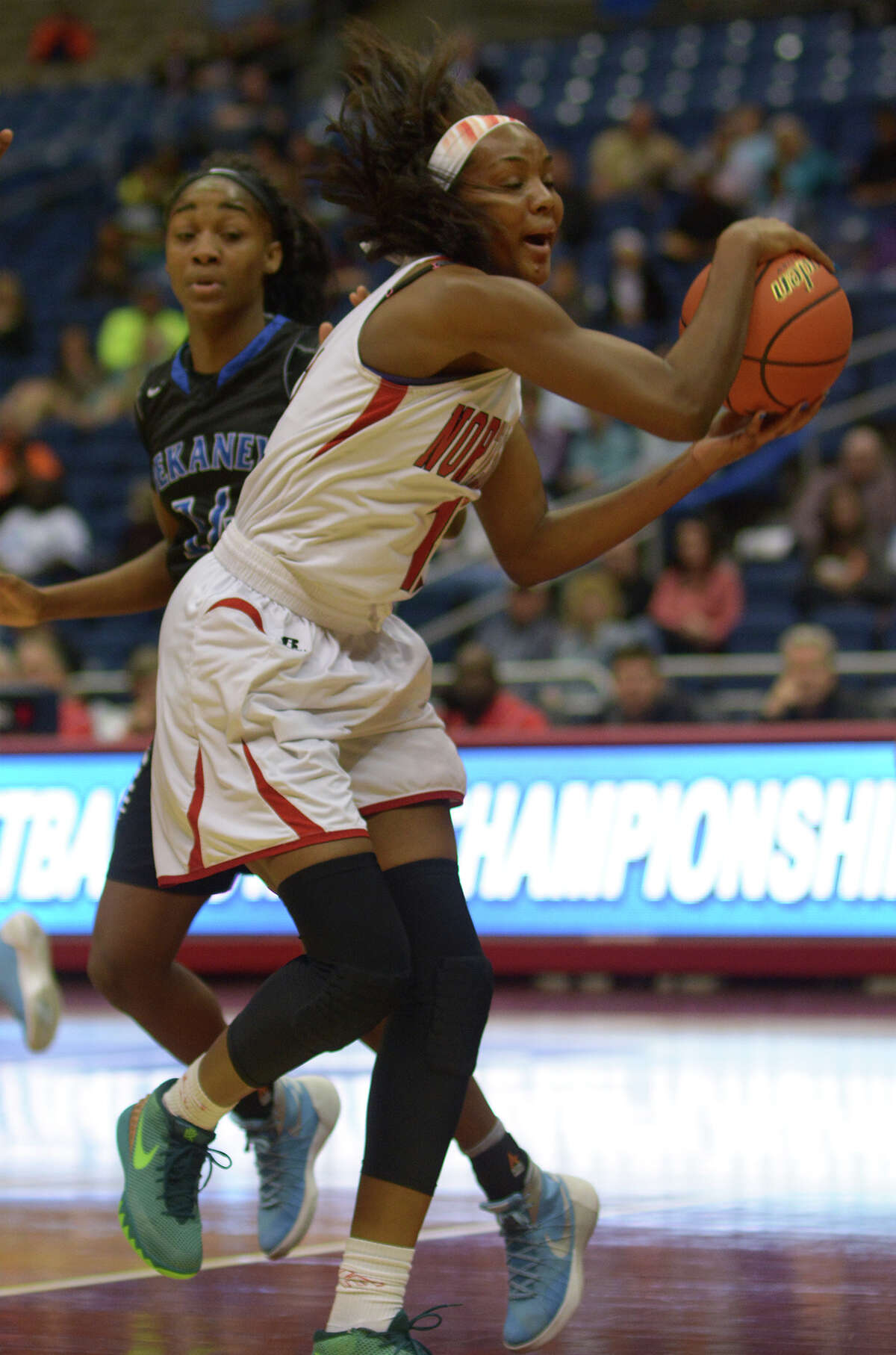 North Shore senior forward Alyssa Okoene (12) pulls a rebound down in front of Dekaney junior guard Keishawna Scott during 1st quarter action of their Class 6A girls basketball state semifinal at the Alamodome in San Antonio on Friday, Mar. 4, 2016. (Photo by Jerry Baker/Freelance)