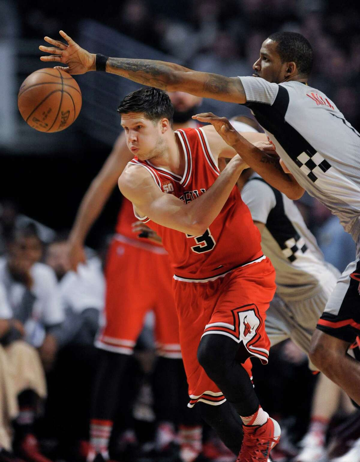Chicago Bulls' Doug McDermott (3) and Houston Rockets' Trevor Ariza (1) go for a loose ball during the first half of an NBA basketball game Saturday, March 5, 2016, in Chicago.