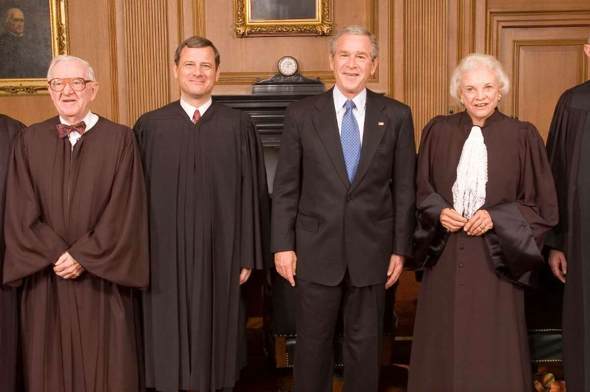 Chief Justice John Roberts poses for pictures with President George W. Bush and senior Justices John Paul Stevens and Sandra Day O'Connor in the Chief Justice's Conference Room Monday morning Oct. 3, 2005, at the Supreme Court in Washington, D.C.