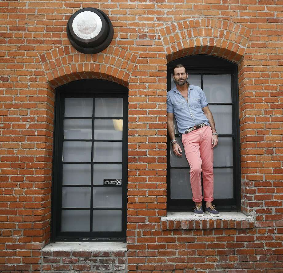 Dockers' chief creative officer Doug Conklyn once thought he wanted to go to West Point. Instead, he brought a soft military influence to the clothing line he oversees, from the brand's iconic khakis to the blue shirt and pink pants he's pictured in here. Photo: Liz Hafalia, The Chronicle