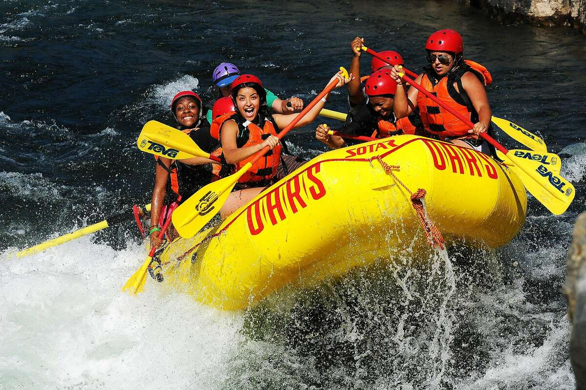 Experienced O.A.R.S. guides steer rafts through rapids on the American River.