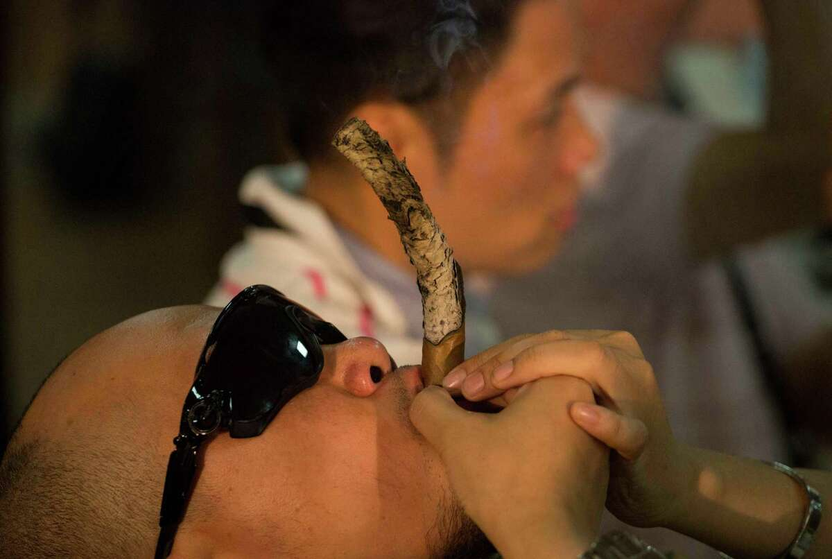 Cigar enthusiast Tan Yung Quiang of China, smokes a cigar during the
