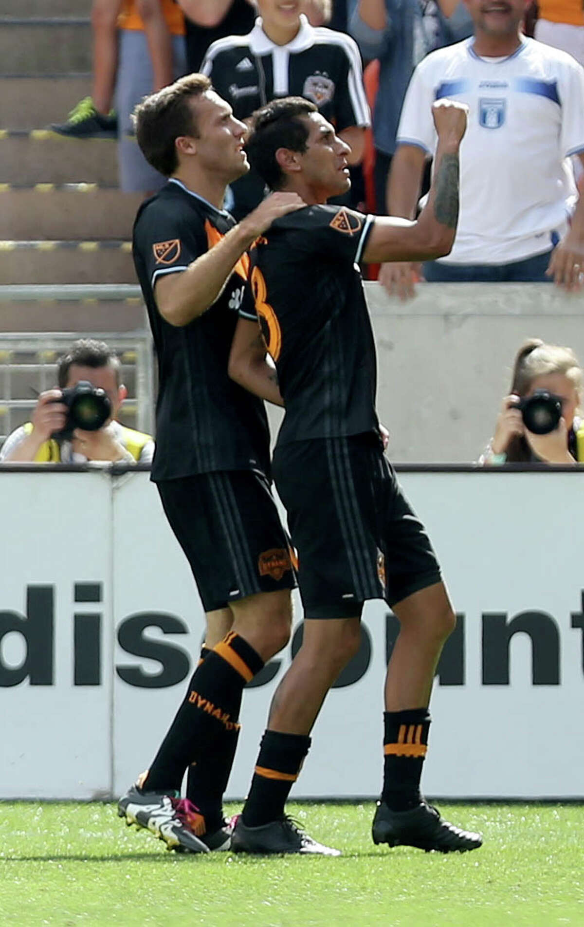 Houston Dynamo midfielder Cristian Maidana (8) celebrates wit teammate Houston Dynamo forward Andrew Wenger (11) after scoring a goal against the New England Revolution in the first half at BBVA Compass Stadium Sunday, March 6, 2016, in Houston.