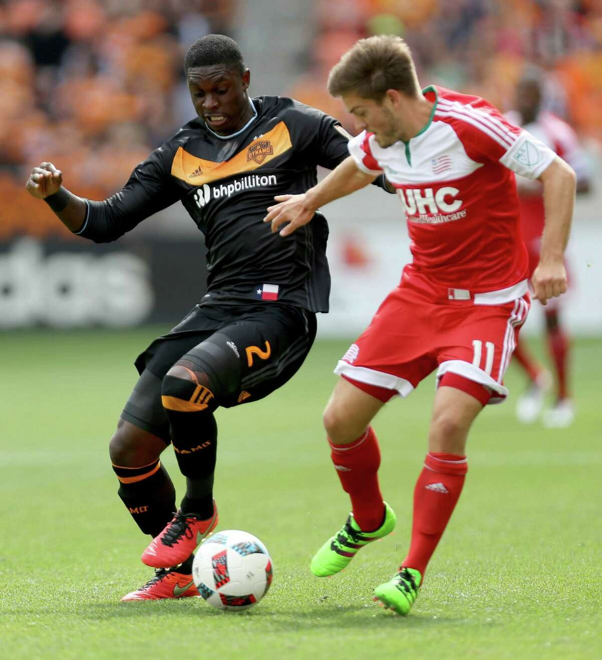 Houston Dynamo defender Jalil Anibaba (2) and New England Revolution midfielder Kelyn Rowe (11) in the first half at BBVA Compass Stadium Sunday, March 6, 2016, in Houston.