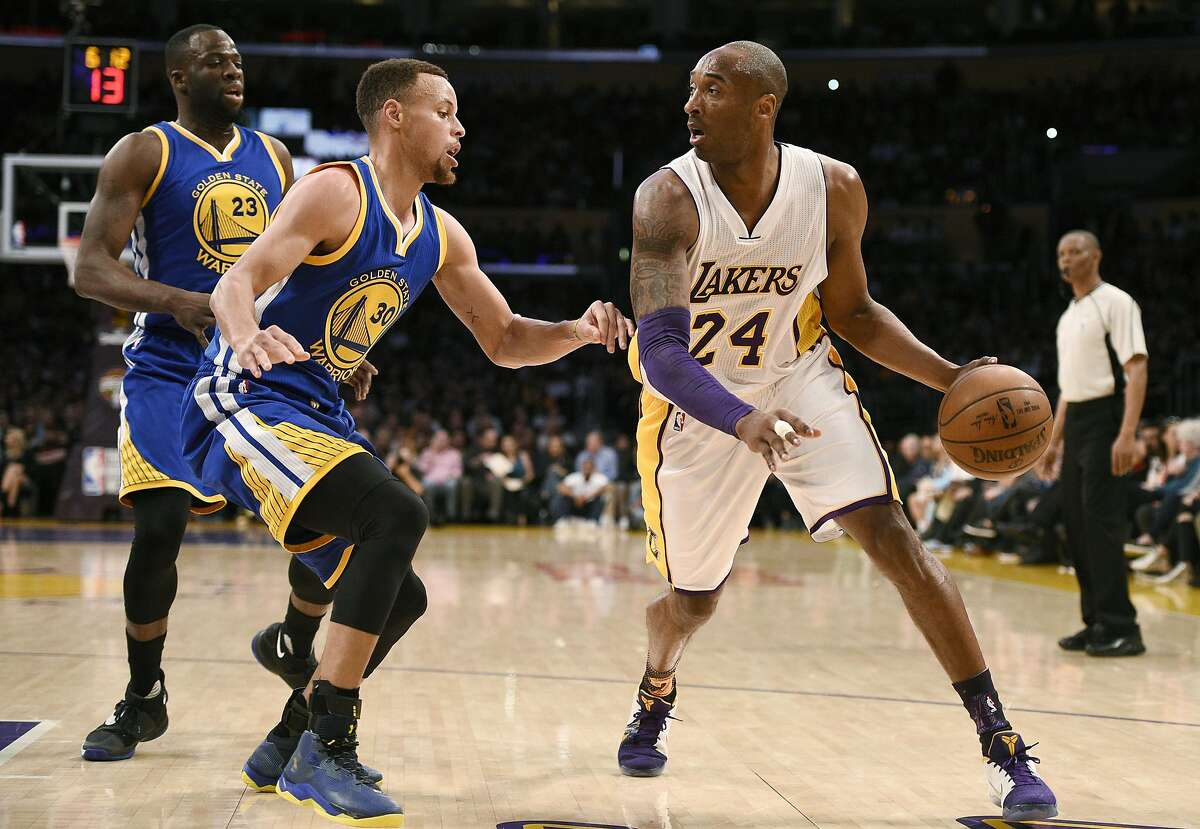Los Angeles Lakers forward Kobe Bryant, right, handles the ball while Golden State Warriors guard Stephen Curry, left, defends during the first half of an NBA basketball game in Los Angeles, Sunday, March 6, 2016.