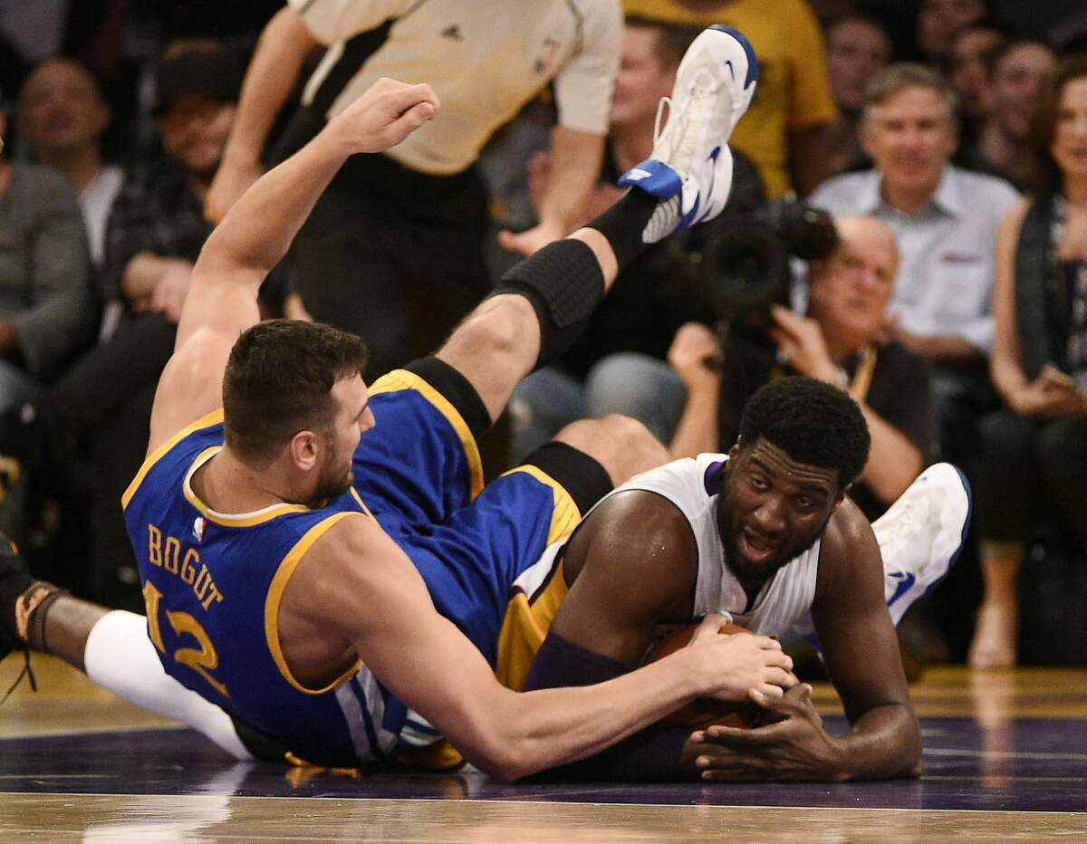 Los Angeles Lakers center Roy Hibbert, right, battles Golden State Warriors center Andrew Bogut, left, for the ball during the first half of an NBA basketball game in Los Angeles, Sunday, March 6, 2016. (AP Photo/Kelvin Kuo)