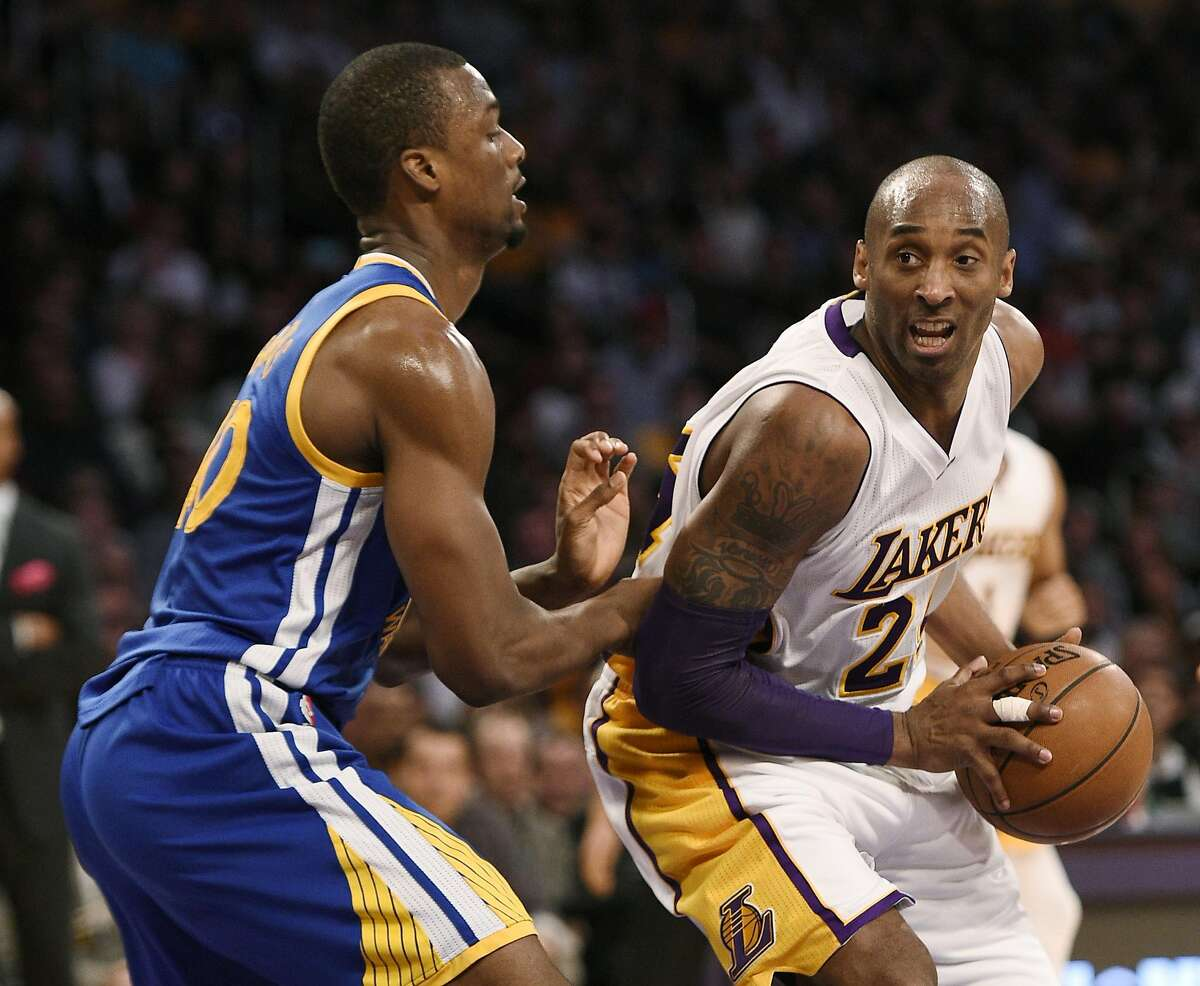 Los Angeles Lakers forward Kobe Bryant, right, handles the ball while Golden State Warriors forward Harrison Barnes, left, during the first half of an NBA basketball game in Los Angeles, Sunday, March 6, 2016.